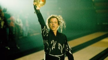 McCracken holds the bowling ball into the air in celebration.