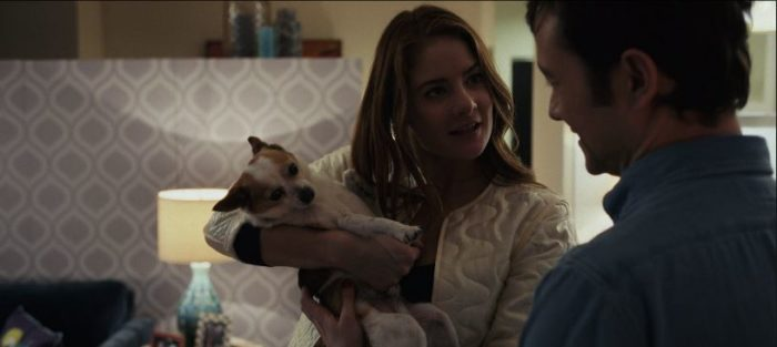 Lindsey holds her dog Liam in her arms in her apartment, showing him to Josh