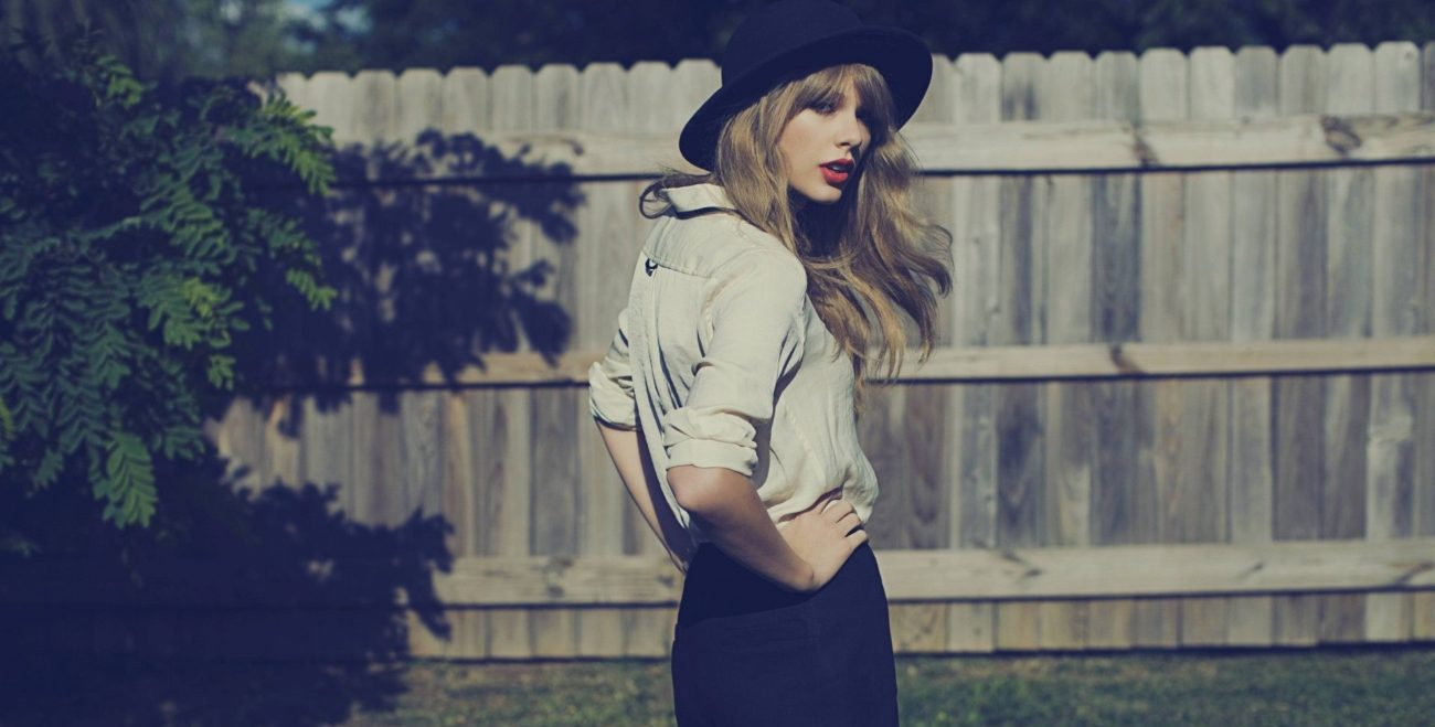 Taylor Swift stands in a yard with a wooden fence in the background, her hands on her hips as she wears shorts and a hat, looking back toward the camera