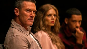 Lars (Luke Evans), Jessica (Samara Weaving), and Ben (Melvin Gregg) stare toward the camera wearing looks of disbelief in the Hulu original series Nine Perfect Strangers