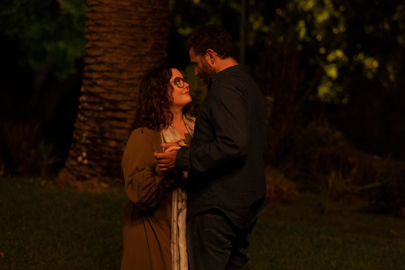 Frances (Melissa McCarthy) and Tony (Bobby Cannavale) slow dance together in the grass in the Hulu Original Series Nine Perfect Strangers