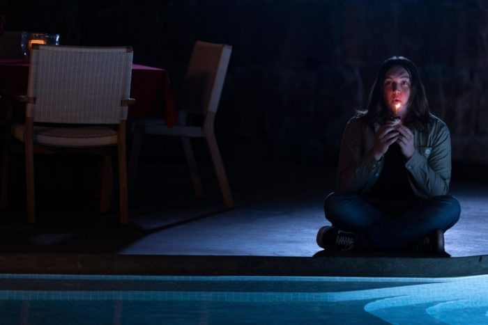 Zach (Hal Cumpston) sits alone by the pool while holding a candle to his face.