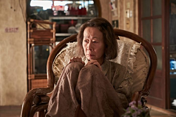 Alzheimer's sufferer Soon-ja (Youn Yuh-jung), mother to Joong-man, sits huddled in front of the TV