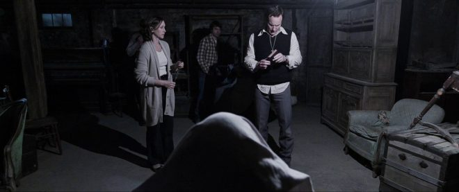 Ed (Patrick Wilson) and Lorraine Warren (Vera Farmiga) perform an exorcism on a possessed Carolyn Perron (Lili Taylor) while her husband Roger (Ron Livingston) watches on in horror.