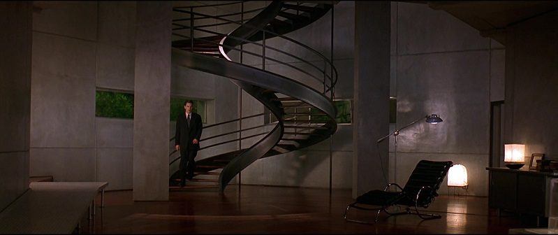 In this image from Gattaca, the character Vincent (Hawke) is depicted in an extreme long shot descending a spiral staircase in an architecturally modern home.