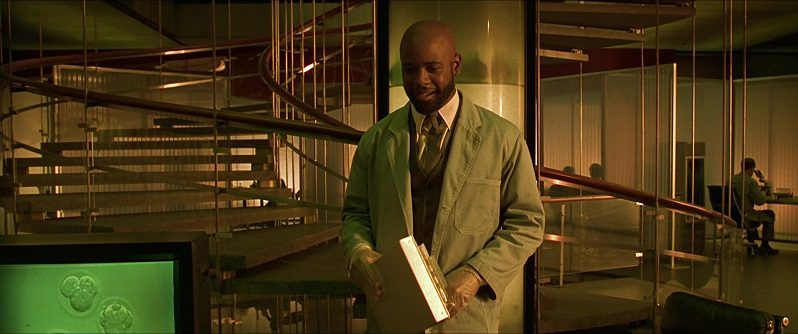 In this image from Gattaca, a geneticist played by Blair Underwood is depicted in a white laboratory coat in front of a spiral staircase in a modern office building.