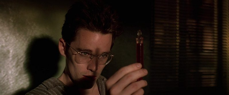 In this image from Gattaca the character Vincent Freeman (played by Ethan Hawke) is depicted in shadowy close-up, holding a vial of blood for inspection.