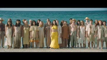 Lorde: Solar Power music video, Lorde stands on the beach surrounded by her sun seeking cohorts