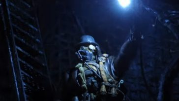 Explorer in a gas mask holds a light up in the dark