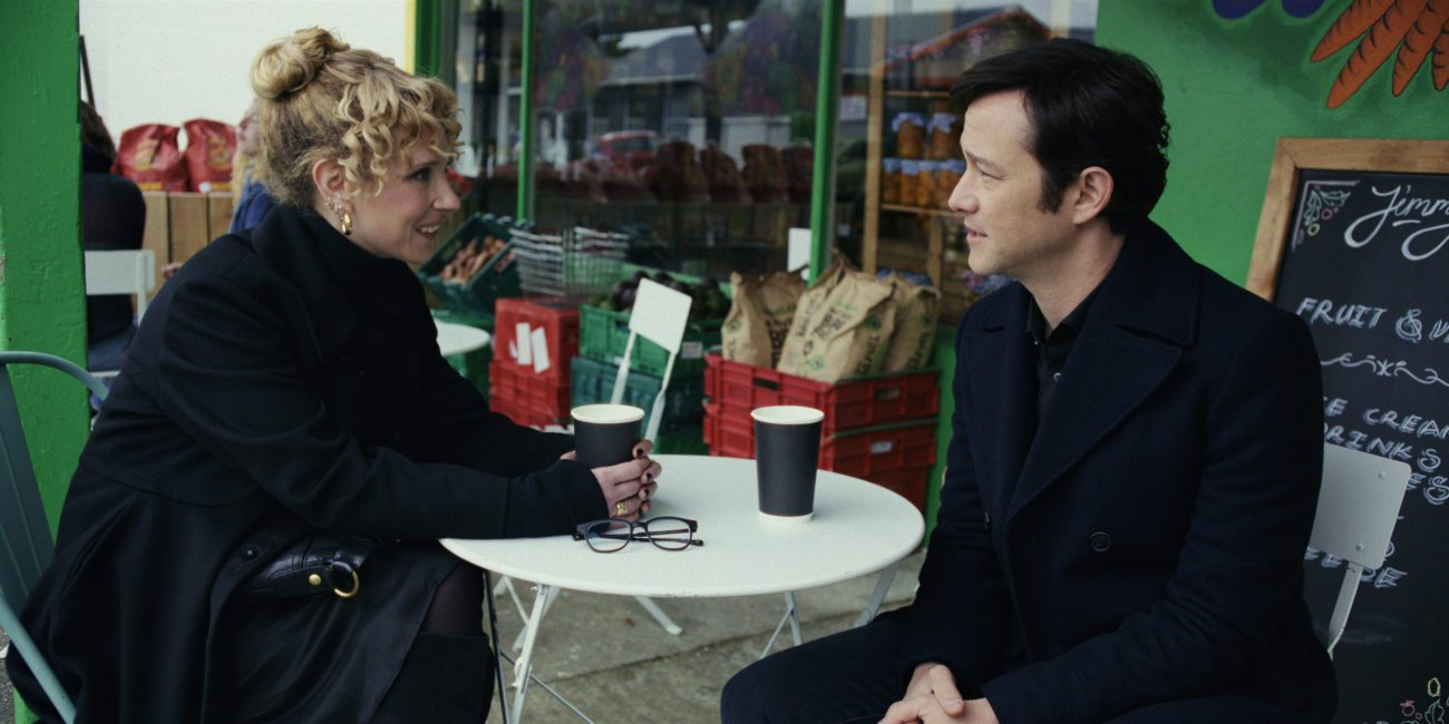 Josh and Megan sit looking at each other across a small table outdoors in Mr. Corman S1E6 Funeral