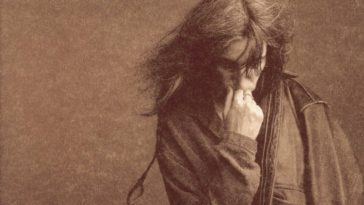 A sepia-tone album cover of the album Gone Again. Patti Smith stands in front of a blank wall with her hand down and her hand to her face.