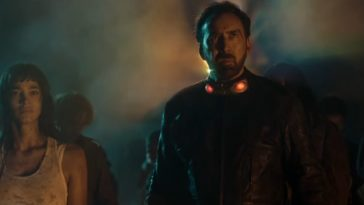 Sofia Boutella stands beside Nicolas Cage against a foggy background