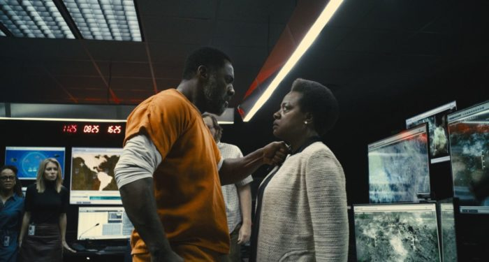Bloodsport stands close to hold a blade to Amanda Waller's throat.