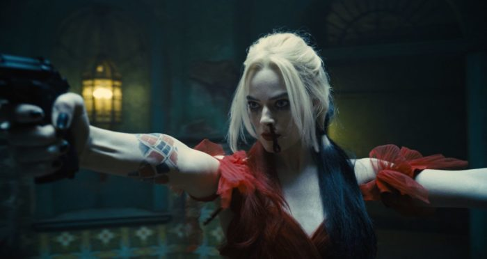 Harley Quinn holds up her two guns for combat.