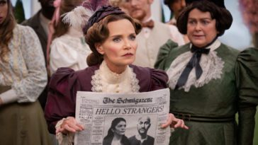 """Mrs. Layton (Kristin Chenoweth) standing in the middle of a group of citizens holding a newspaper with a picture of Josh and Mel and the headline """"Hello Strangers"""" on the front page and looking intently toward the crowd"""