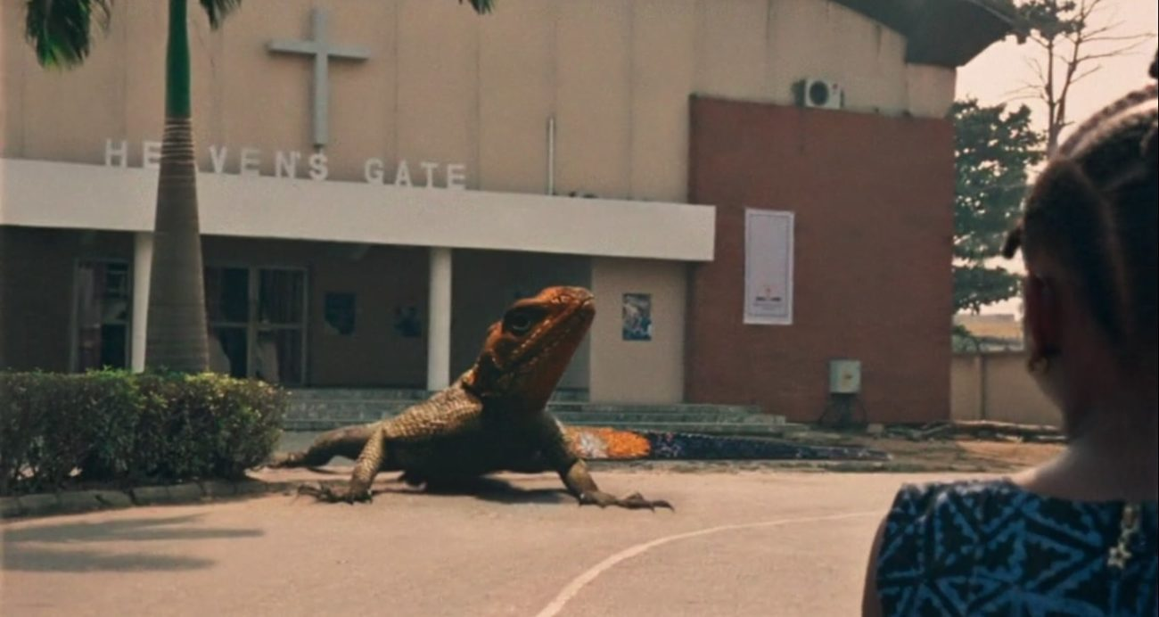 Screenshot from the Criterion Channel short film Lizard. Juwon has her back to us as she looks at a giant lizard in front of the church.