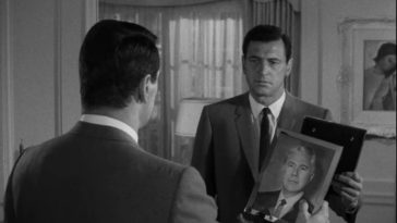 """In this image from Seconds, Antiochus """"Tony"""" Wilson (Rock Hudson) is depicted gazing into a mirror image of himself and holding a portrait of his former self Arthur Hamilton (John Randolph)."""