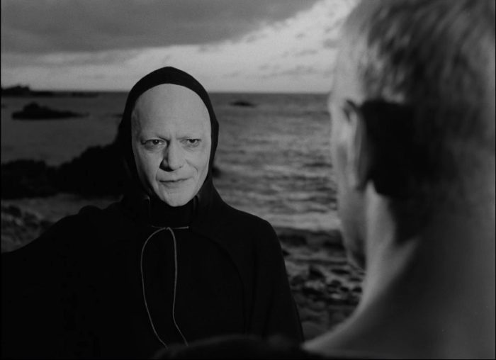 In this image from The Seventh Seal, Death (played by Bengt Ekerot) confronts Antonius Block (Max von Sydow) on a rocky shore.