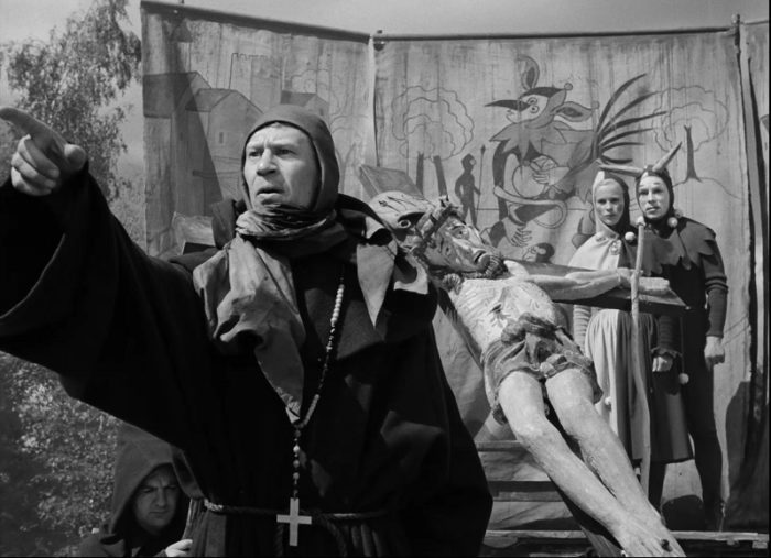 In this image from The Seventh Seal, a monk (played by Anders Ek) addresses an audience as Jof and MIa listen in costume from their stage alongside an effigy of Christ on the cross.