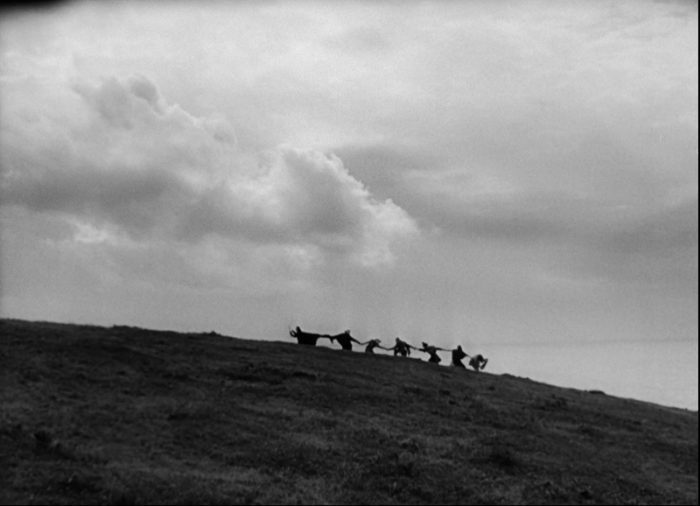 In this image from The Seventh Seal, Death is depicted leading his six victims in a dance along the hillside.