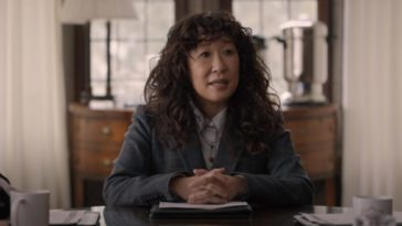 Professor Ji-Yoon Kim (Sandra Oh) sits at the head of a conference table with windows behind her and two people on the edges of the frame
