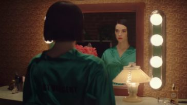St Vincent stares into a vanity mirror with a serious look on her face donning a green silk robe with her name written on the back