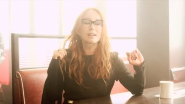 Tori Amos sits in a cafe booth wearing a black dress with her eyes closed in the Trouble's Lament music video