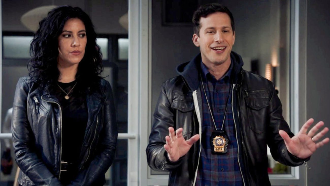 Jake and Rosa stand side by side. Jake has his hands out in front of him as if he is explaining something