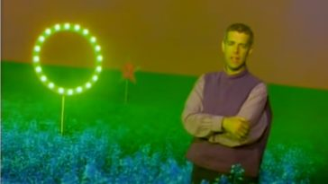 The singer (Neil Tennant) in a purple vest and shirt stays on the CGI field background (including the circle formed with bright lightbulbs to his right) with his arms folded.