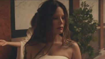 Halsey looks to the side, dressed in white