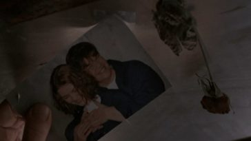 A photo of Janette and Sonny, and a dried rose, taped to the underside of a bunk bed