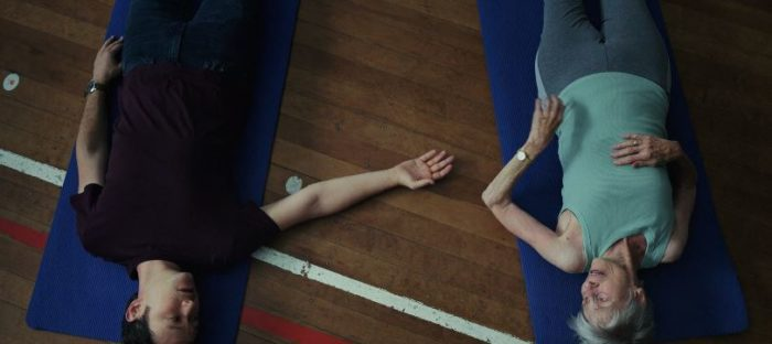 Josh reaches a hand over to an older woman as they both lie on mats on the floor during the breathing class