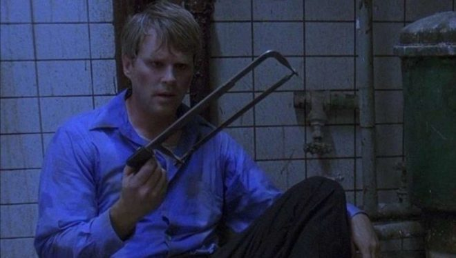 Kidnapped and handcuffed in an abandoned room, Lawrence Gordon (Carey Elwes) contemplates using a hacksaw to cut himself to freedom.
