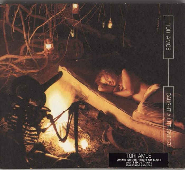 """Tori Amos lays on a mattress near a small bonfire on the cover of the """"Caught a Lite Sneeze"""" single."""