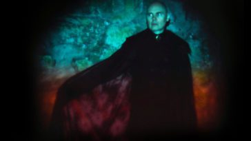 Billy Corgan poses against a green light background