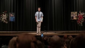 A young man stands on stage under a spotlight.