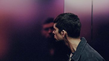 A man peers deep into his reflection in an elevator