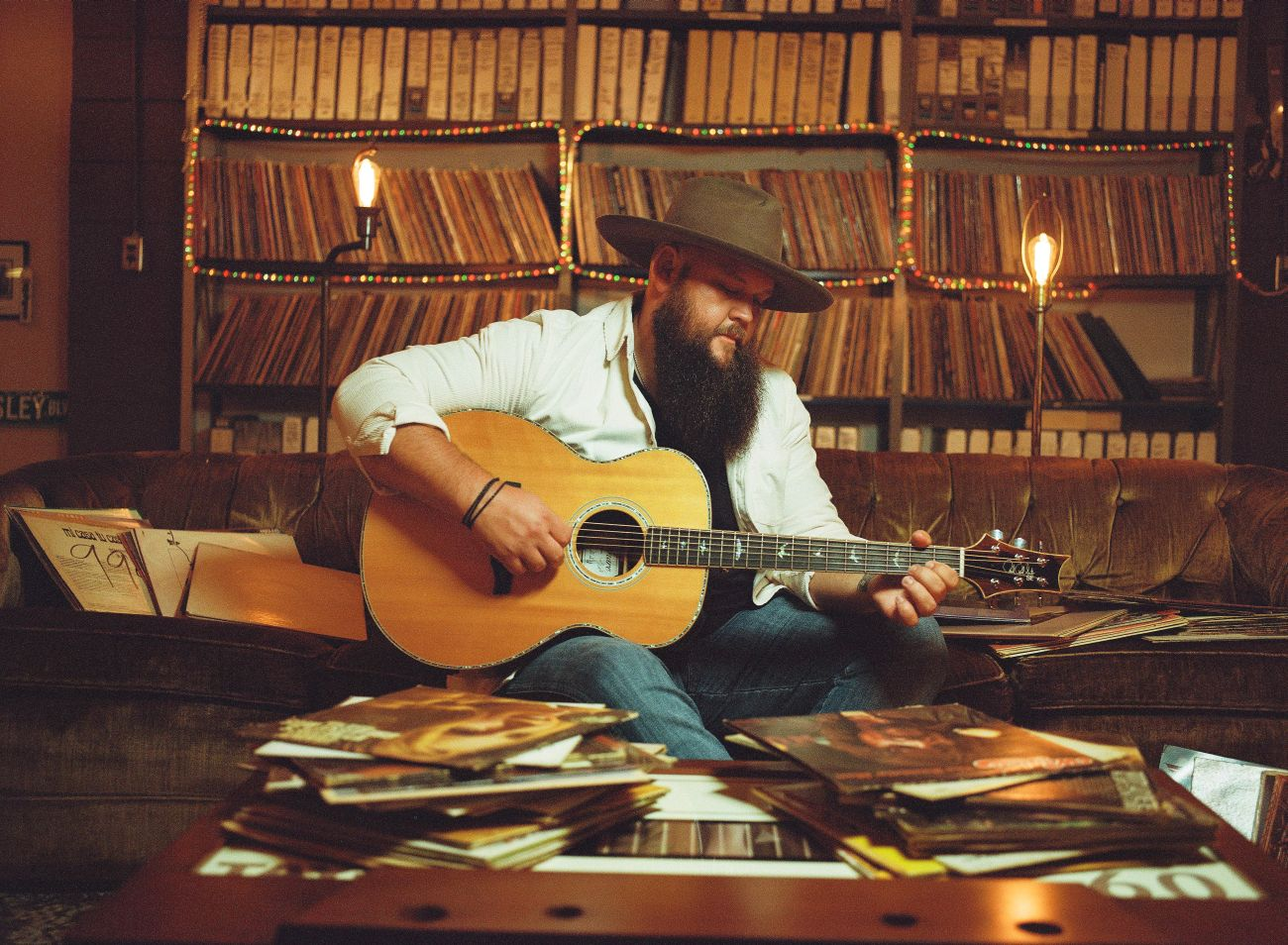 Larry Fleet strums his guitar with stacks of records behind him