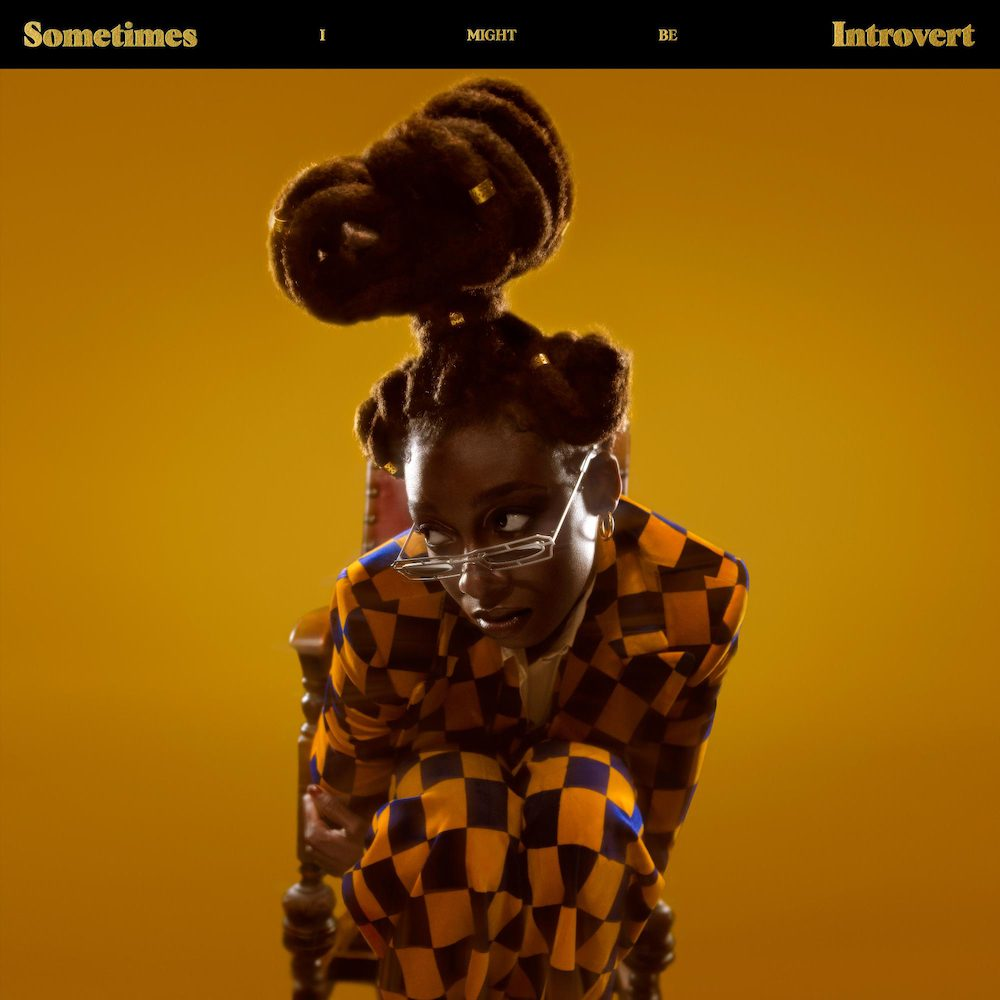 Sometimes I Might Be Introvert: Little Simz sits hunched over shyly in a small chair, wearing a noisy chequered suit that matches the backdrop. Her hair is magnificent.