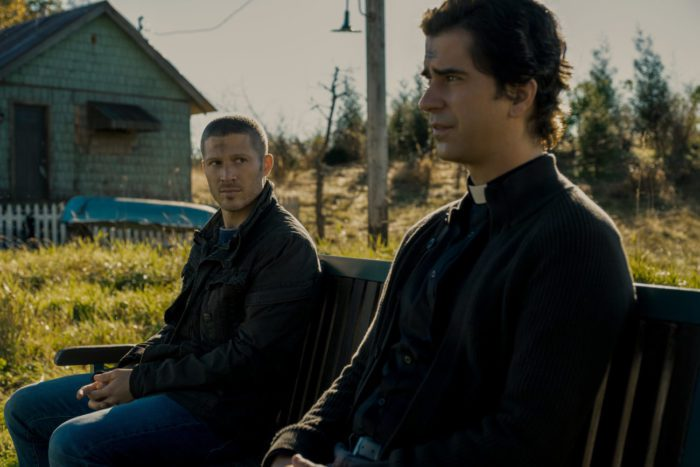 Riley Flynn (Zach Gilford) speaks with Father Paul (Hamish Linklater).