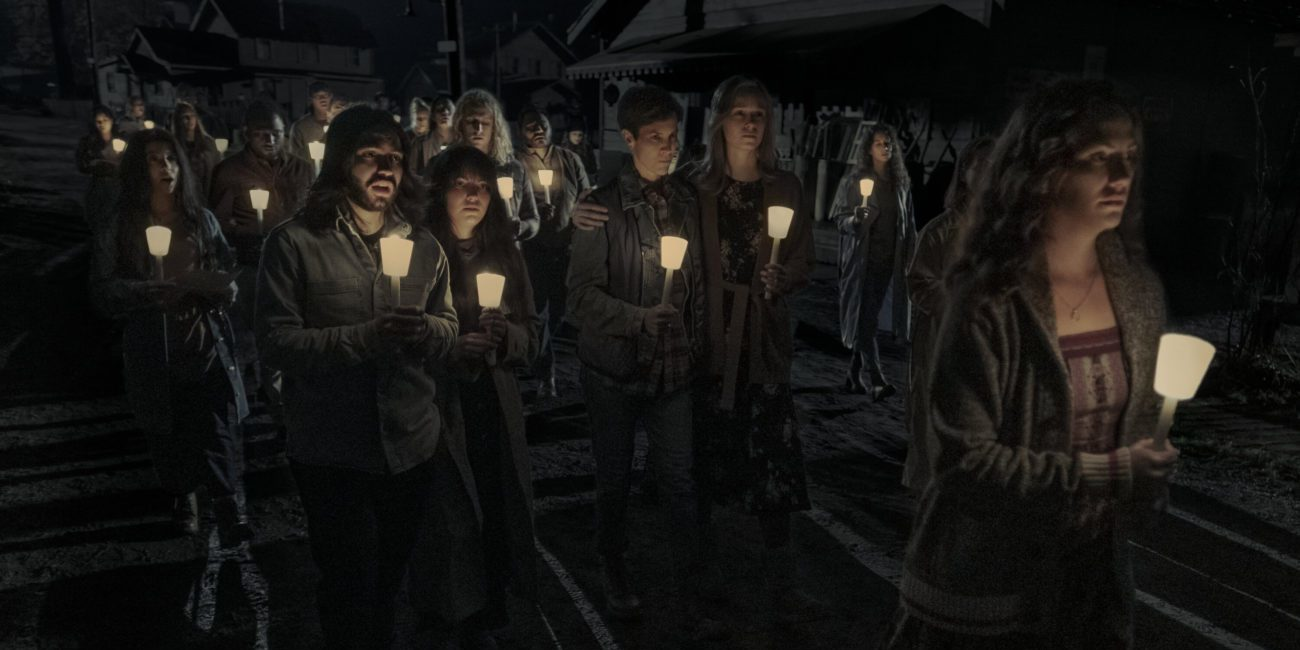 Erin Greene (Kate Siegel) leads a group in a candle light vigil.