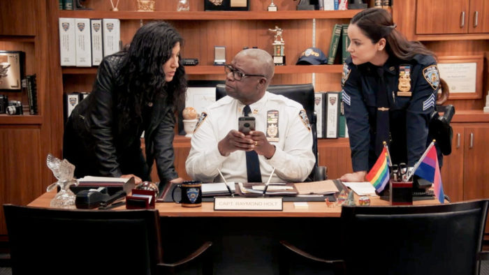 Amy and Rosa stand next to Holt at his desk