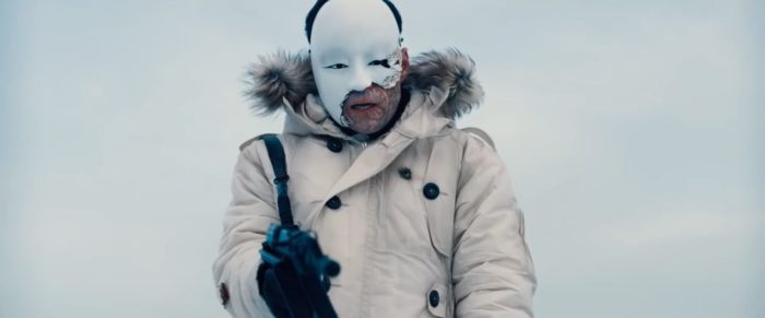 Safin aims a gun wearing a heavy winter coat and a porcelain mask