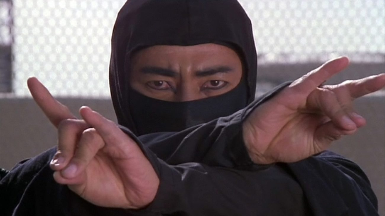 Cho, in ninja garb, crosses his arm in a stance.