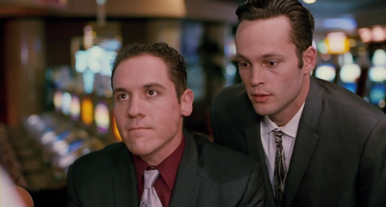 A man looks at a card dealer while his friend behind him whispers advice.