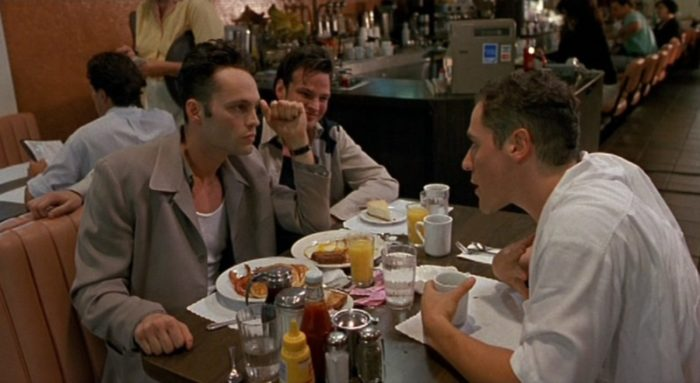 Three friends share a conversation at a diner.