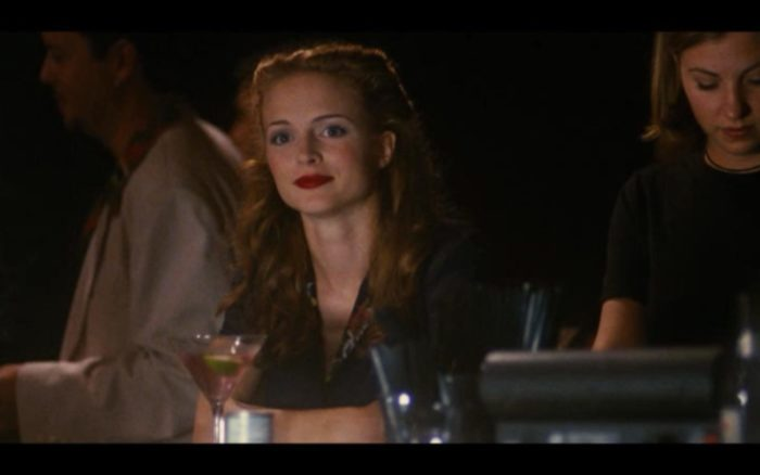 A blond woman looks over from the bar.