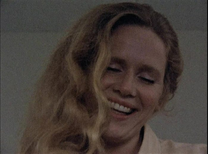 In this image from the 1973 series Scenes from a Marriage, Marianne (Liv Ullmann) is depicted smiling, in close-up, with her eyes nearly closed and hair down.