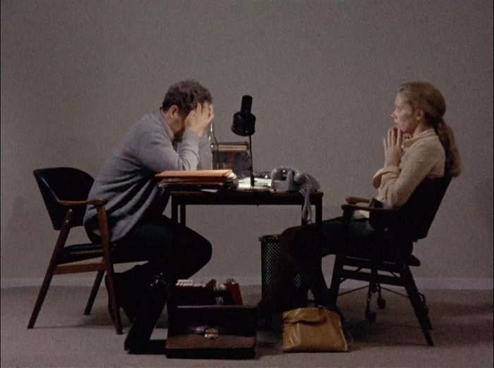 In this image from the 9173 Scenes from a Marriage, Johan (Erland Josephson) and Marianne (Liv Ullmann) are depicted facing each other over a small table, he with his head in his hands.
