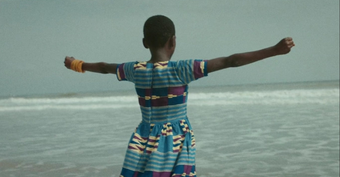 Still from Da Yie. A young girl stands triumphantly in front of the ocean.